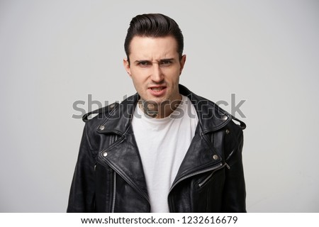 A young motorcycle racer looks angry, argues, defends his opinion, eyebrows frowned, fiery eyes, mouth ajar, dressed in black leather jacket, with a stylish hairstyle in grease, over white background ストックフォト ©