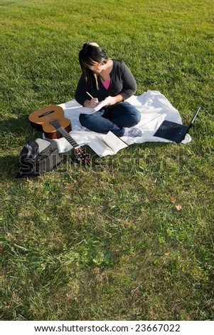 A young musician writing in her notebook while sitting in the grass on a nice day.