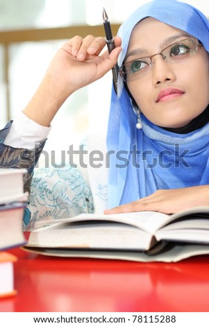 A young muslim girl reading a book while thinking