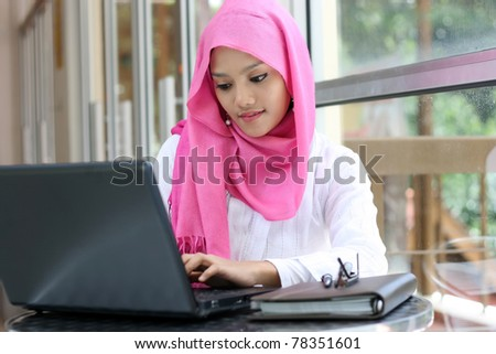 A young muslim woman using laptop