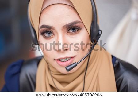 A young muslim women customer support operator with headset and smiling