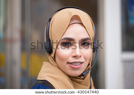 A young muslim women with headset smiling at camera in call center