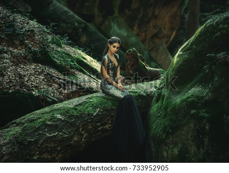 A young mysterious girl - a dark princess sits on a log among the rocks. Gothic photosession theme of Halloween. Unusual, creative outfit #733952905