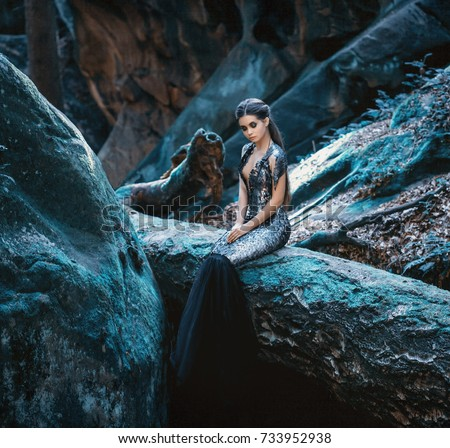 A young mysterious girl - a dark princess sits on a log among the rocks. Gothic photosession theme of Halloween. Unusual, creative outfit #733952938