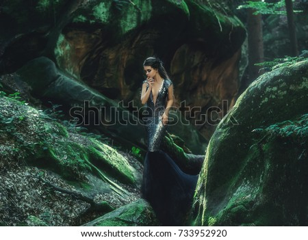 A young mysterious girl - a dark princess walks among the rocks. Gothic photosession theme of Halloween. Unusual, creative outfit #733952920