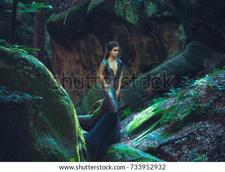 A young mysterious girl - a dark princess walks among the rocks. Gothic photosession theme of Halloween. Unusual, creative outfit #733952932