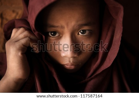 A young novice monk covered his head by robe