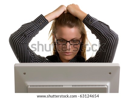 A young office worker pulls her hair in frustration of a computer crash.