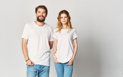 A young pair of white t-shirts stands nearby