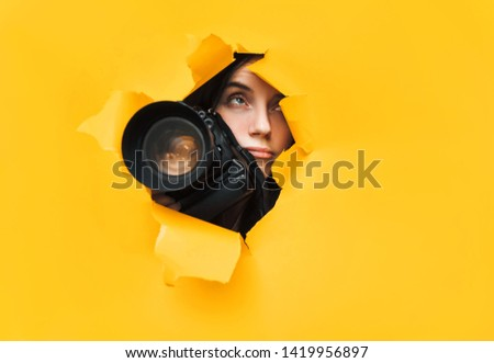 A young paparazzi girl holds a reflex camera and looks through a torn hole in yellow paper. The concept of embarrassment, sadness, disappointment, despondency and upset. Copy space.