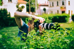 A young photographer capturing beautiful green leaves in the garden with his professional camera