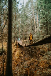 A young photographer in a yellow jacket sits on a suspension bridge and takes pictures of the river beneath him. A man in the middle of a suspension bridge.