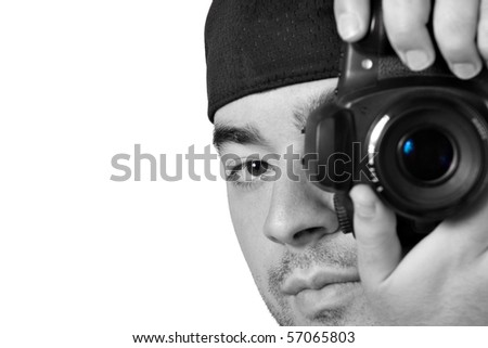 A young photographer taking a photo with his digital single lens reflex camera with selective color.
