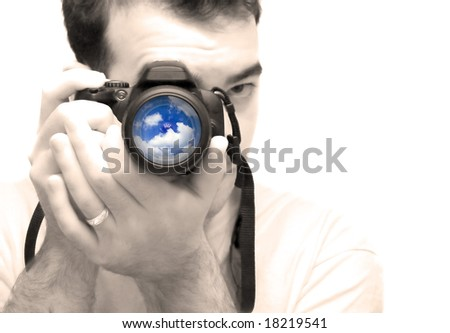 A young photographer taking a shot with his DSLR camera.  Selective color and shallow depth of field.