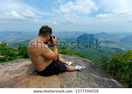 A young photographer with a naked torso takes a picture from the top of the mountain. Photographs beautiful valleys and clouds.