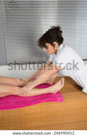 A young physical therapist giving a leg massage in a health center