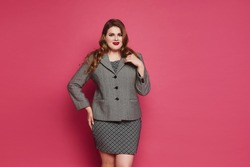 A young plump woman with bright makeup and red full lips wearing office clothes posing on the pink background. Plus-size model girl in grey dress and suit coat over pink background