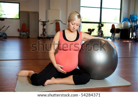 A young pregnant woman doing relaxation exercise using a fitness ball while sitting on a mat and holding her tummy