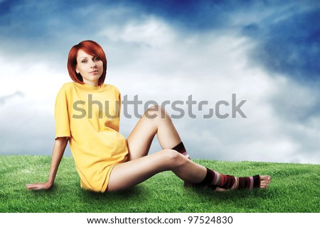 A young pregnant woman in a yellow dress sits on a lawn Photo stock ©
