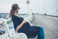 A young pregnant woman is sitting on a bench on the pier