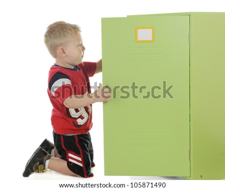 A young preschooler-athlete dressed for sports and into his locker.  The locker label left blank and plenty of space on the locker door for your text.  On a white background.