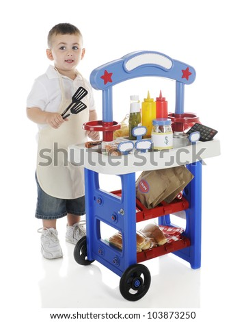 A young preschooler looking up as he tends his hot dog stand.  The stand's signs are left blank for your text.  On a white background. - stock photo