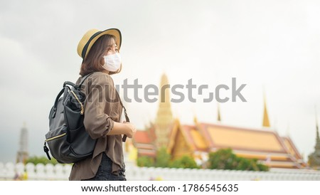 A young pretty Asian woman is wearing protective mask travel around famous places in Bangkok city , New normal travel, covid-19 protection , safe travels , travel under COVID-19, Post- pandemic travel
