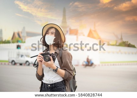A young pretty Asian woman is wearing protective mask traveling around famous places in Bangkok city , New normal travel, covid-19 protection , safe travels