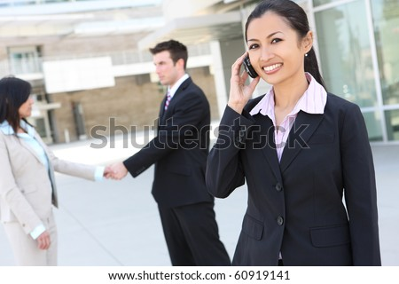 A young pretty asian woman on the phone at office building with team in background