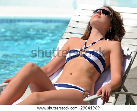 A young pretty Girl sunbathing by the pool