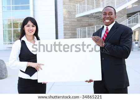 A young pretty indian business woman and african man holding a sign