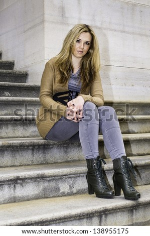 A young pretty woman is sitting on steps to take a break./Portrait of Pretty Woman