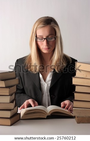 A young pretty woman reading a book and sitting on a table above a white background