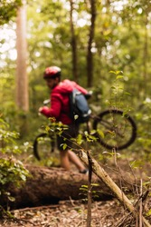 A young professional cyclist in sportswear wearing a helmet outdoors - Young male cyclist carrying his mountain bike in the jungle.