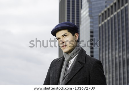 A young professional is standing in the front of  business buildings and looking forward/Hope and Wish