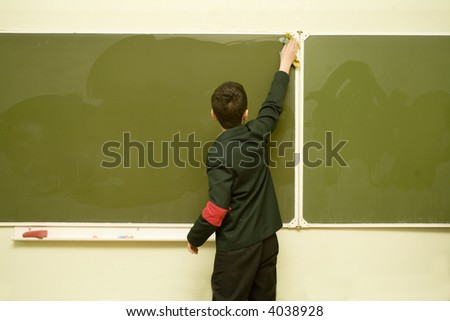 a young pupil is cleaning the blackboard