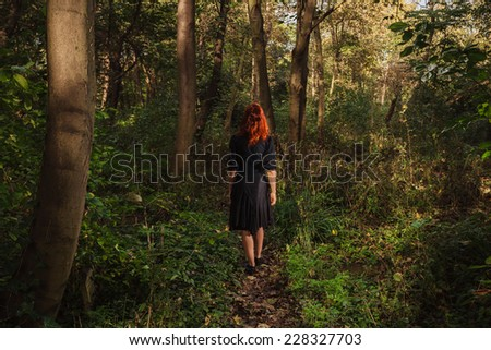 A young redhead woman is walking alone in the woods or enchanted forest