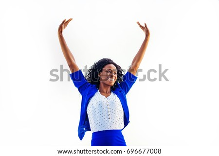 a young relaxed and happy african woman wearing formals standing with her hands up #696677008