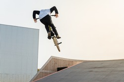 A young rider on a BMX bike does tricks in the air. BMX freestyle in a skate park.