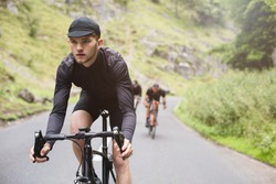 A young road cyclist dressed in black, winning race with friends in Cheddar Gorge, U.K
