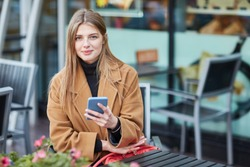 A young Russian girl is typing a message on the phone. Moscow. Autumn. A girl writes SMS message. Communicates in social networks. Woman sitting in a cafe in the city center.