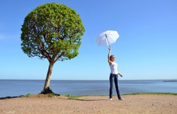 A young Russian woman in a white top and blue jeans standing near a round crown tree and with a white sun umbrella raised high in her hand. Cloudless sky and blue water background, sand upfront.