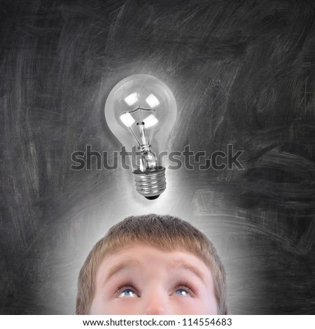 A young school boy is looking up at a glowing light bulb above his head on a black chalkboard. Use it for an idea or education concept.