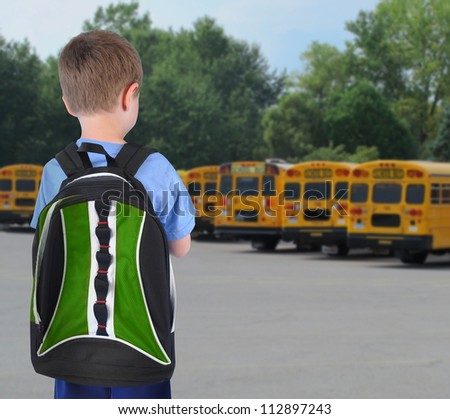 A young school boy is standing with a book bag and looking at school buses in the background.