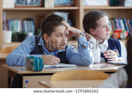 A young schoolboy sitting at a desk in a school class. #1295886562