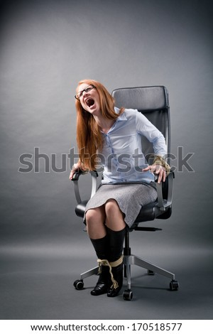 A young secretary or business assistant tied up to an office chair screaming for help.