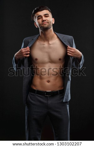 A young sexy man takes off his jacket worn over his naked body against a dark background.