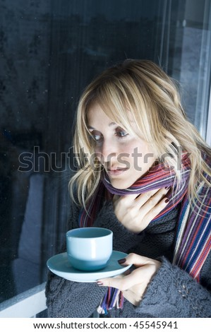 A young sick woman with a cup of tea in her hand. She hold her head in pain.