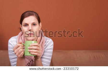 A young sick woman with a cup of tea in her hand. She hold her head in pain. A lot of copyspace.