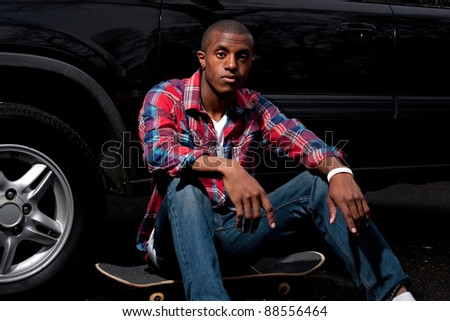 A young skater hanging out seated on his skateboard next to a parked car.
